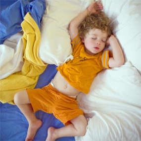 Niño durmiendo en la cama.